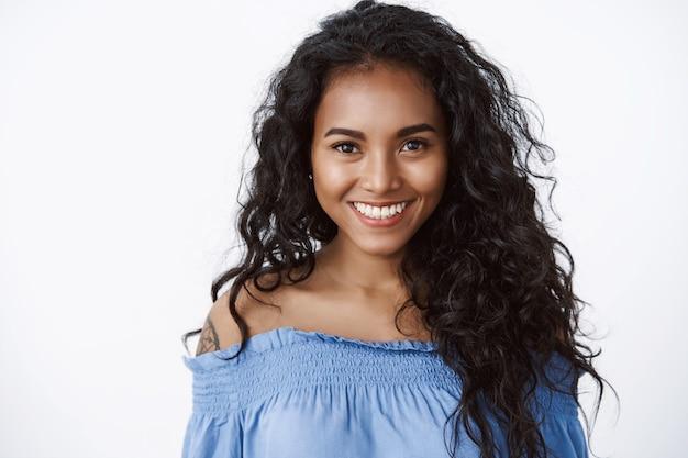 Close-up aantrekkelijke zelfverzekerde en charismatische jonge vrouw met lang krullend haar, draag blauwe blouse, glimlachende toothy en kijk oprecht met zelfverzekerde, aangemoedigde uitdrukking