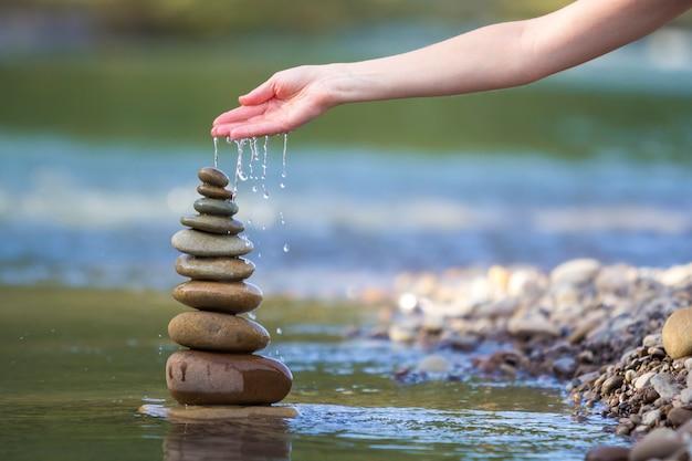 Close-up abstract beeld van het gietende water van de vrouwenhand