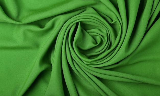 Close-up abstracte textiel achtergrond van spiraalvormige groene gevouwen plooien van stof, verhoogde bovenaanzicht, direct erboven