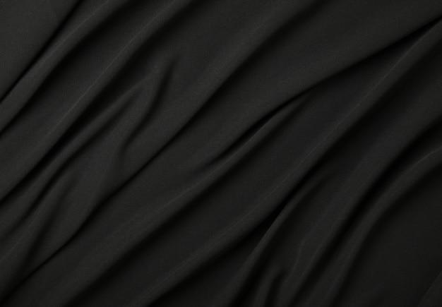 Close-up abstracte textiel achtergrond van zwarte gevouwen plooien van stof, verhoogde bovenaanzicht, direct erboven