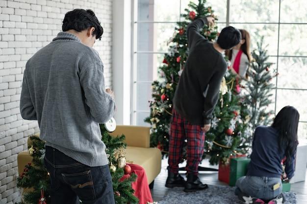 Close-up achter van jonge man versieren van kerstbomen van de kerstviering met vrienden achtergrond. nieuwjaar vieren. prettige kerstdagen en fijne feestdagen.