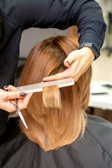 Close-up achteraanzicht van kapper knipt rood of bruin haar aan jonge vrouw in de schoonheidssalon. kapsel in kapsalon