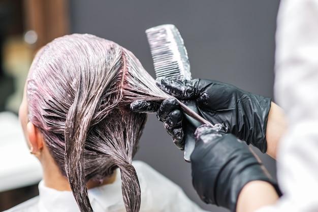 Close-up achteraanzicht van kapper past kleur toe op het haar van de klant in zwarte handschoenen. haarkleuring in een schoonheidssalon. schoonheid en mensen concept.