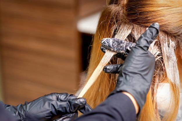 Close-up achteraanzicht van kappers handen in handschoenen die kleurstof aanbrengen op een haarlok van roodharige jonge vrouw in een kapsalon