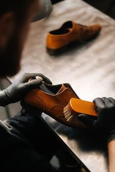 Close-up achteraanzicht van onherkenbare schoenmaker schoonmaken met borstel oude lichtbruine leren schoenen