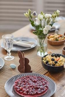 Close-up achtergrond van elegante paastafel set met lentebloemen en heerlijke zelfgemaakte gerechten, kopieer ruimte