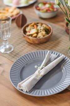 Close-up achtergrond van elegante rustieke eettafel met heerlijke zelfgemaakte gerechten, couvert op de voorgrond, kopieer ruimte