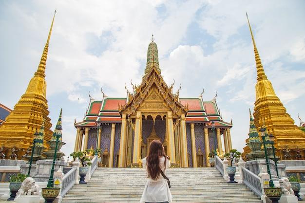 Close-up achterkant portret jonge aziatische vrouw staande voor de gouden kerk in wat phra kaew, er is een van de meest favoriete tempels in bangkok thailand.