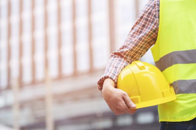 Close-up achterkant weergave van technische mannelijke bouwvakker stand houden gele veiligheidshelm en reflecterende kleding dragen voor de veiligheid van de werkzaamheden. buiten van gebouw.