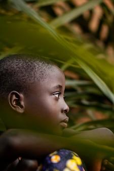 Close-up afrikaanse jongen poseren met bladeren
