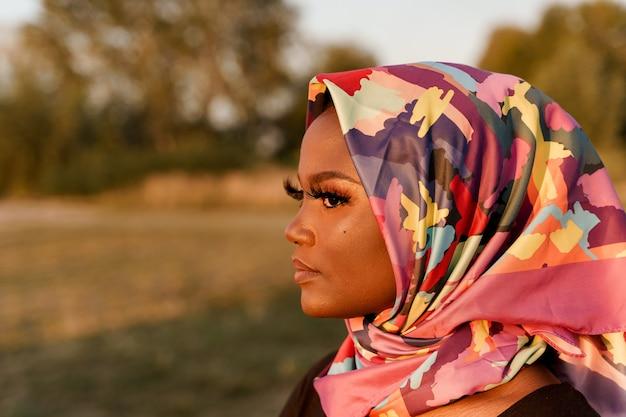 Close-up afrikaanse zwarte vrouw weared in sjaal genaamd hijab op zoek naar links