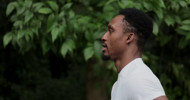 Close-up afro-amerikaanse man loopt in het park op een zonnige dag, zijaanzicht. train 's ochtends buiten in het stadspark cardio. gezonde levensstijl activiteit.