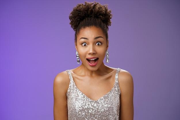 Close-up afro-amerikaanse onder de indruk sprakeloos jong meisje open mond verbaasd hijgen wijd open ogen verbaasde blikken onder de indruk ontvangen interessant amusant voorstel, staande blauwe achtergrond.