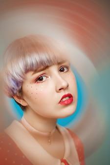 Close-up artistiek conceptueel portret van mooi popachtig meisje met kort licht violet haar, gekleed in rode jurk over blauwe muur onscherpe voorgrond.