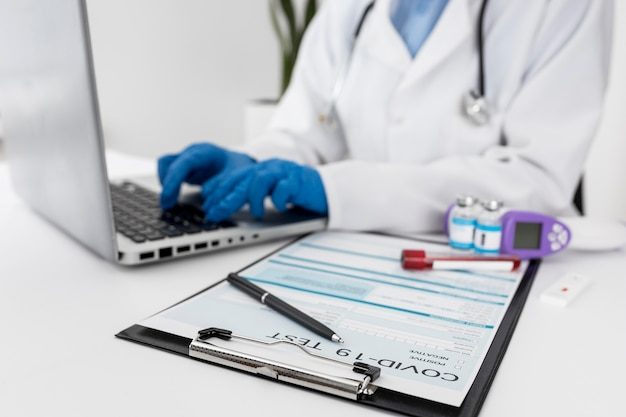 Close-up arts die aan laptop werkt