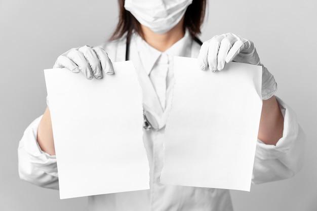 Close-up arts met chirurgische masker bedrijf papieren