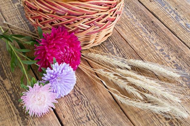 Close-up aster bloemen, rieten mand en tarwe oren op houten achtergrond.