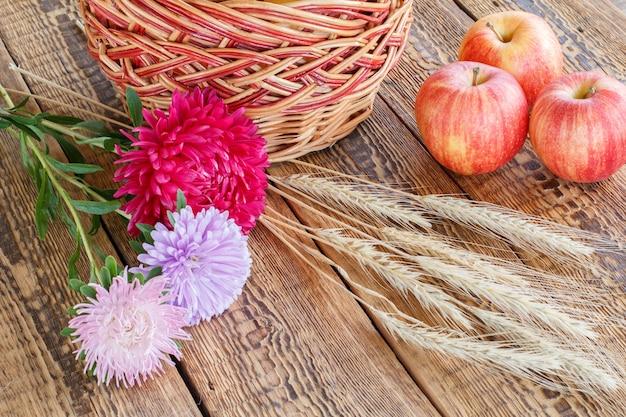 Close-up aster bloemen, rieten mand, rode appels en tarwe oren op houten achtergrond.