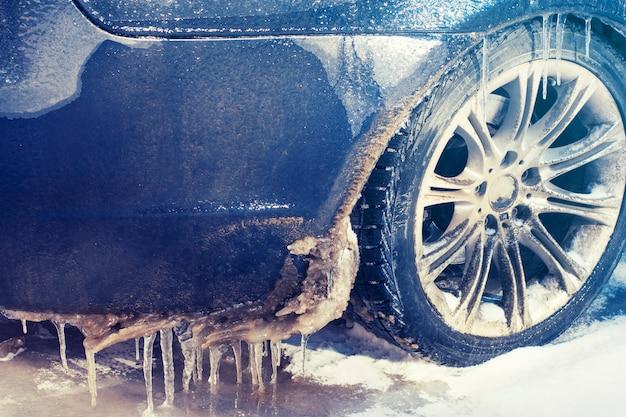 Close-up autowiel in ijspegels en ijzel. ernstige ijsvorming.