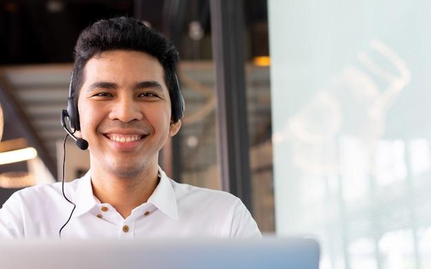 Close-up aziatische call center medewerker man aan het werk lachend met service-mind