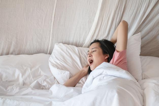Close-up aziatische die vrouw na ontwaken in de ochtend wordt uitgerekt