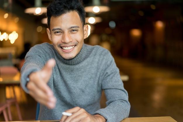 Close-up aziatische knappe man outstretching arm voor make-handshake