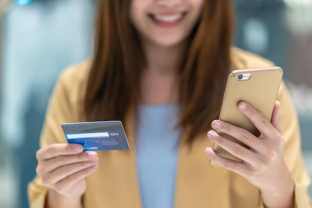 Close-up aziatische vrouw die creditcard met mobiel voor online het winkelen in warenhuis gebruiken