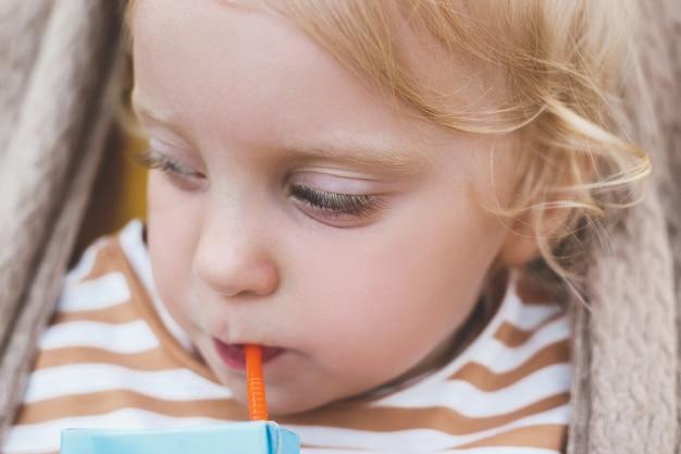 Close-up babymeisje drinken met stro. hoge kwaliteit foto