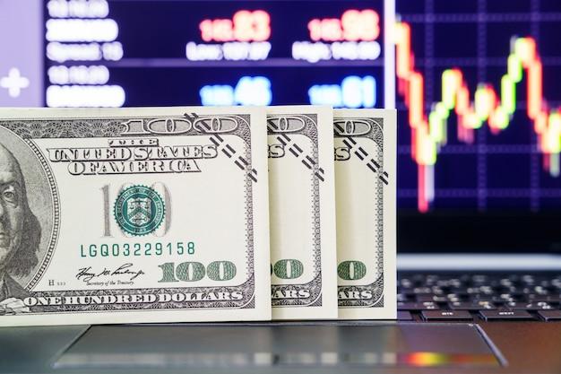 Close-up bankbiljetten op toetsenbordcomputer met handelsbeursmarktprijsgrafiek op de achtergrond
