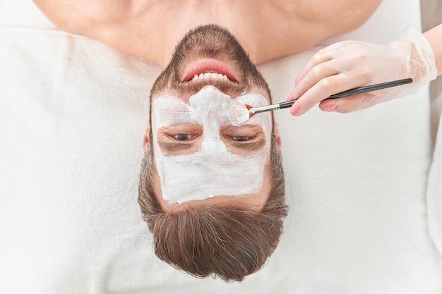 Close-up bebaarde jonge man is ontspannen terwijl schoonheidsspecialist witte klei op zijn gezicht verspreidt
