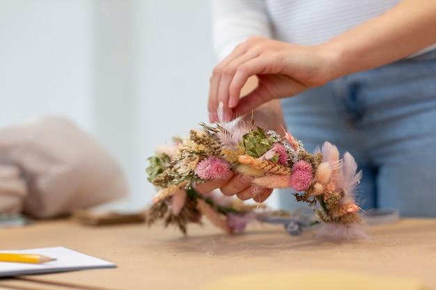 Close-up bedrijfspersoon het creëren van een krans van bloemen