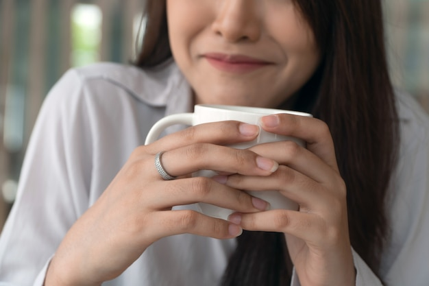 Close-up bedrijfsvrouw glimlacht en houdt een witte koffiekop in koffiewinkel.