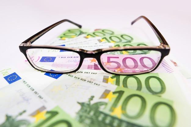 Close-up beeld van 500 euro zichtbaar door de lens van een bril.