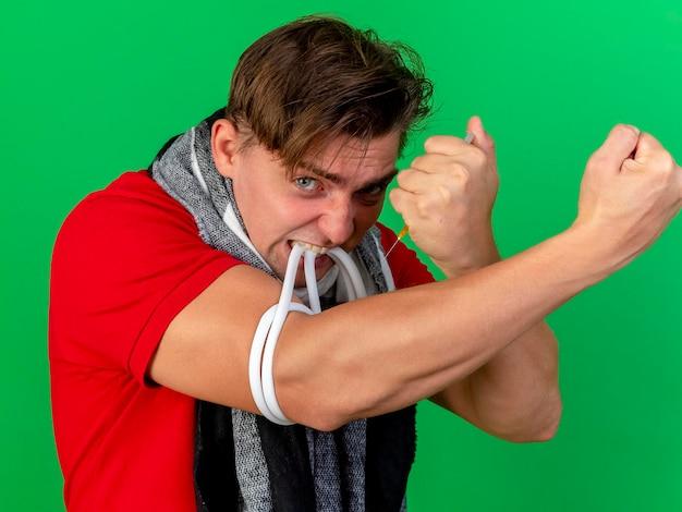 Close-up beeld van bang jonge knappe blonde zieke man met sjaal aanscherping harnas met tanden injectiespuit te houden voor zichzelf en kijken naar voorzijde geïsoleerd op groene muur
