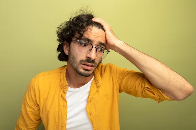 Close-up beeld van bezorgde jonge knappe man met bril hand op het hoofd neerkijkt geïsoleerd op olijfgroene muur