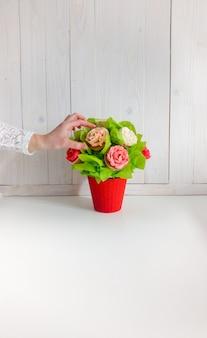 Close-up beeld van bloemen in boeket gemaakt van cupcakes en taarten op tafel in café of bakkerij. mooie foto van snoep en gebak op witte achtergrond