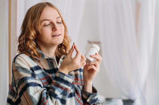 Close-up beeld van blonde vrouw witte ronde pil aanbrengend mond.