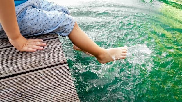 Close-up beeld van blootsvoets peuterjongen zittend op de houten brug bij het meer en opspattend water met zijn voeten