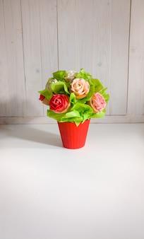 Close-up beeld van boeket in rode pot gemaakt van cupcakes tegen witte houten achtergrond. mooie foto van snoep en gebak op witte achtergrond