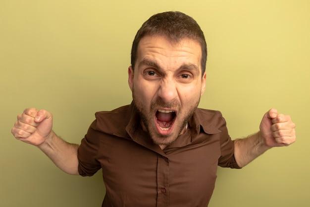 Close-up beeld van boze jonge man balde vuisten schreeuwen geïsoleerd op olijfgroene muur