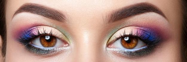 Close-up beeld van bruine vrouwelijke ogen met avondmake-up. kleurrijke roze en blauwe smokey eyes.