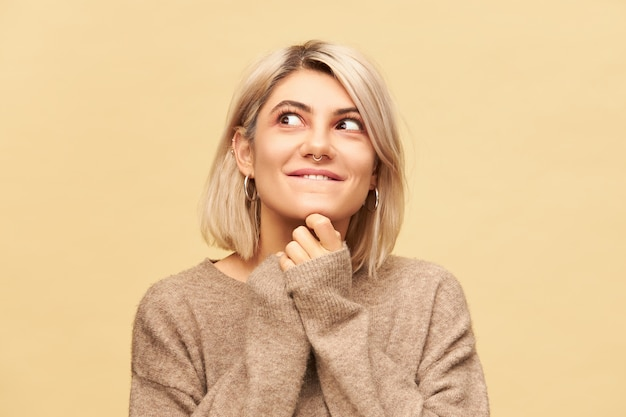 Close-up beeld van charmante jonge blonde vrouw draagt neusring en bob kapsel hand in hand onder haar kin en wegkijken met een speelse mysterieuze glimlach, grappen uithalen en kattenkwaad uithalen