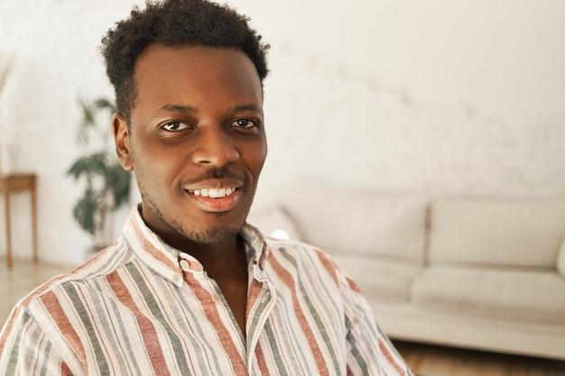 Close-up beeld van coole vrolijke donkere jongeman met afro kapsel zitten in een stijlvolle woonkamer interieur, thuis ontspannen, camera kijken met brede, gelukkige glimlach.