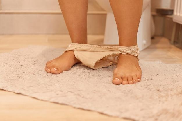 Close-up beeld van de blote benen en voeten van een vrouw met haar kanten slipje liggend op de badkamervloer rond haar enkels, vrouw staande in de buurt van toilet op zacht tapijt.