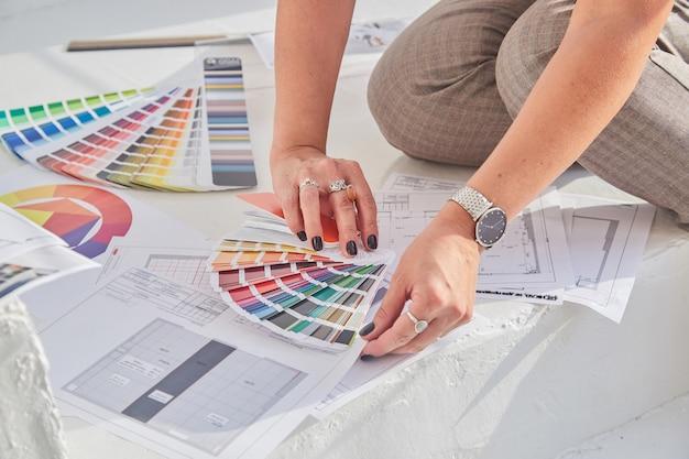 Close-up beeld van de handen van de interieurontwerper vrouw werken met kleurenpalet en interieurplannen voor een nieuw project met soft focus sea ...