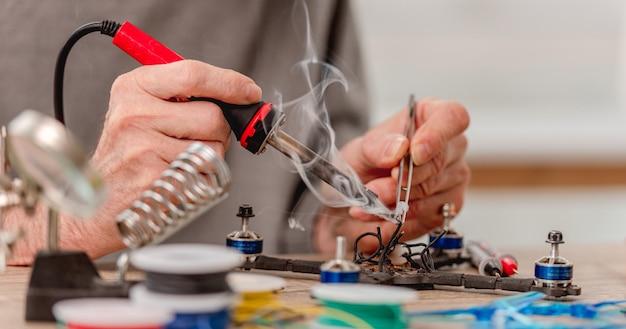Close-up beeld van de handen van de mens tijdens het reparatieproces van de quadcopter met behulp van soldeerbout voor draden