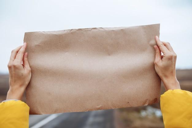 Close-up beeld van de handen van een vrouw die een gele jas draagt met een blanco posterpapier aan de kant van een lege winterweg.