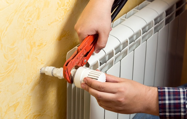 Close-up beeld van de man die verwarmingsradiator en aansluitklep installeert