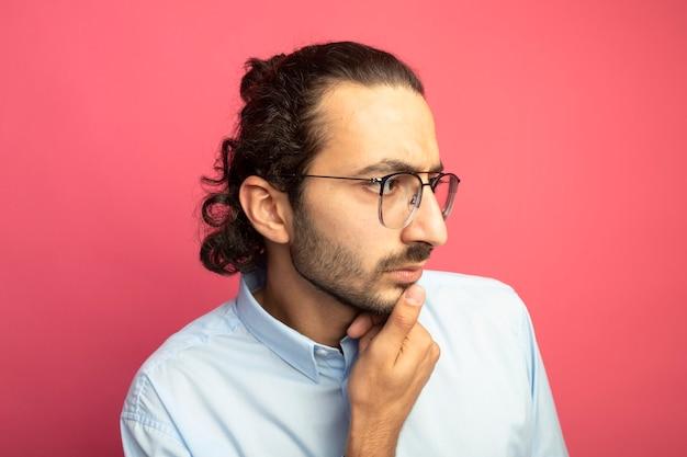 Close-up beeld van doordachte jonge knappe blanke man met bril aanraken van de kin op zoek naar kant geïsoleerd op een karmozijnrode achtergrond