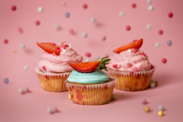 Close-up beeld van drie kleurrijke cupcakes met aardbeien op roze oppervlak met vallende snoepjes